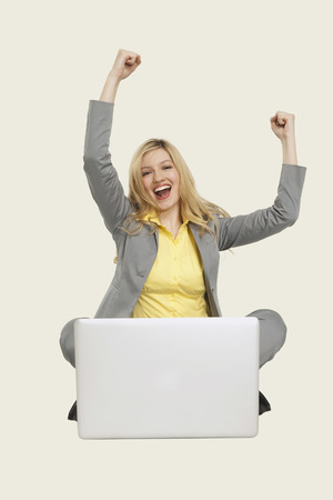 clenching: Businesswoman with laptop, clenching fist. Stock Photo