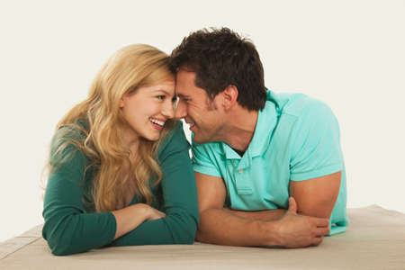 rubbing noses: Couple lying on floor rubbing noses smiling Stock Photo