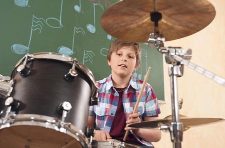 Jongen spelen drums op muziekles Stockfoto