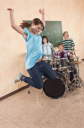 Students at music class girl jumping boy playing drums classmates standing behind photo