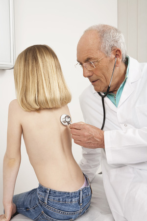 listening back: Doctor examining girl with stethoscope Stock Photo