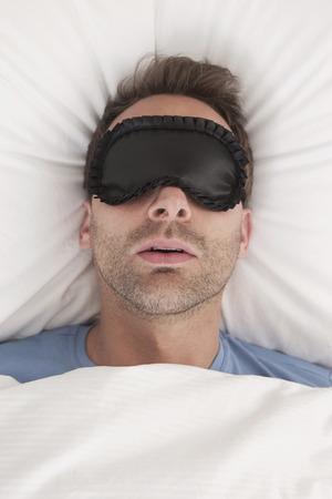 sleep mask: Germany, Man wearing sleep mask sleeping Stock Photo