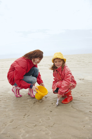 Germany, St.Peter-Ording, North Sea, mother and daughter  playing on beach smiling