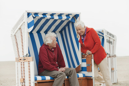 Germany, North Sea, St.Peter-Ording, senior couple man resting on hooded beach chair woman standing on side photo