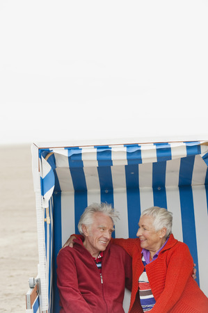 Germany, North Sea, St.Peter-Ording, Senior couple sitting on hooded beach chair photo