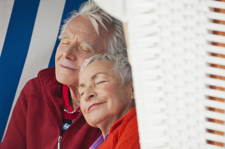 Germany, North Sea, St.Peter-Ording, Senior couple resting on hooded beach chair, close-up photo