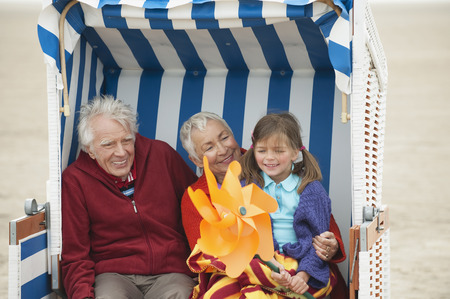 Germany, St. Peter-Ording, North Sea, Girl (6-7) sitting with grandparents on hooded beach chair photo