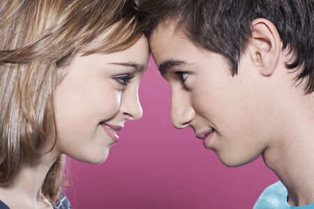 Attractive teenage girl and boy looking at each other smiling