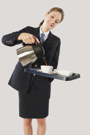 Young air hostess pouring hot beverage photo