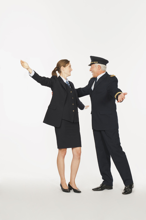 Senior captain and young air hostess hugging on white background Stock Photo