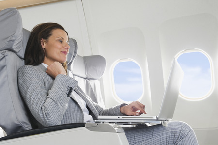 travellers: Businesswoman using laptop on airplane Stock Photo