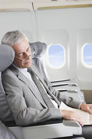 Senior passenger sleeping on airplane
