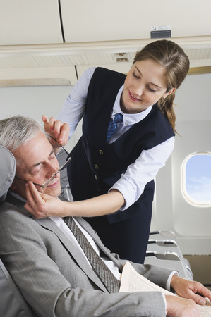 Senior passenger sleeping on airplane while air hostess is removing glasses