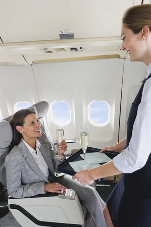 Air hostess serving champagne to businesswoman on airplane