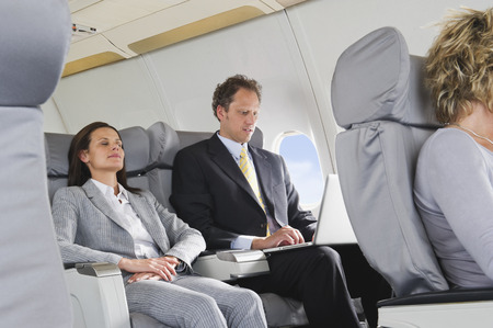 first plane: Businesswoman sleeping and businessman working on laptop on airplane