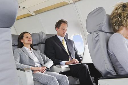 Geschäftsfrau schläft und Geschäftsmann auf Laptop auf Flugzeug Lizenzfreie Bilder