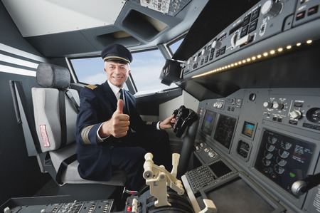 Senior flight captain with thumbs up in airplane cockpit photo