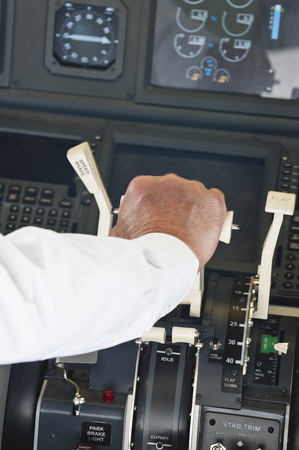 thrust: Pilot turning switching thrust lever in airplane cockpit