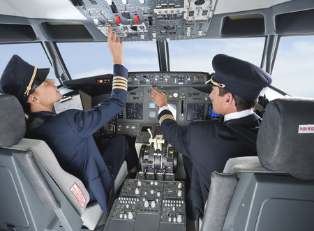 Pilot pushing button in airplane cockpit with co-pilot photo