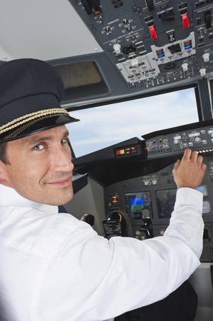 Pilot driving airplane in cockpit smiling photo