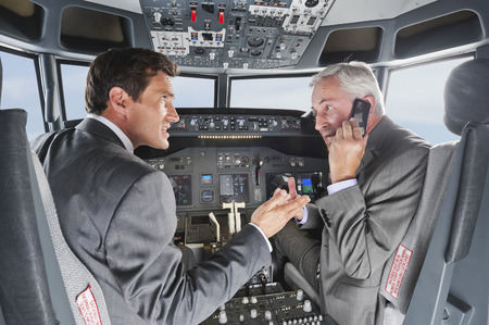 Two businessmen flying airplane in cockpit and using mobile phone at the same time Фото со стока