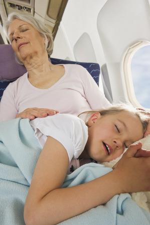Senior woman and girl sleeping  on airplane photo