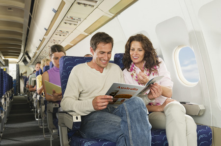 Passengers reading book on airplane