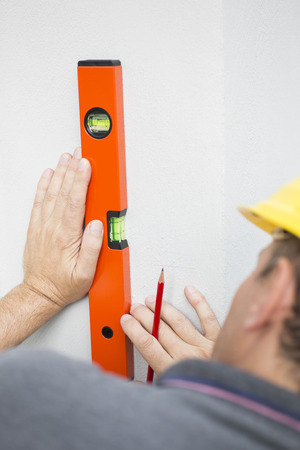 depth measurement: Construction worker measuring walls straightness with spirit level