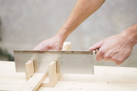miter: Manual worker working with wood saw and miter box
