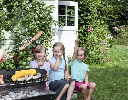grill tongs sausage: Group of girls sitting in garden waiting someone offering barbequed sausage
