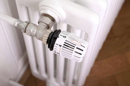regulators: White radiator with white thermostat