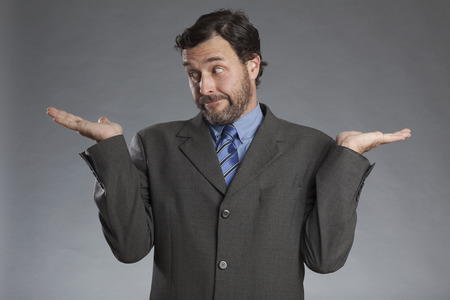 sceptic: Skeptical businessman with both palms upwards against gray background Stock Photo
