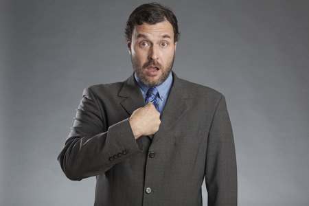 Businessman pointing at himself against gray background Stockfoto
