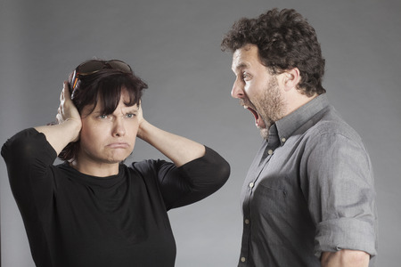 Mature couple quarreling man shouting woman covering ears photo