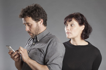 curiously: Mature couple man busy using smartphone woman looking curiously over mans shoulders Stock Photo