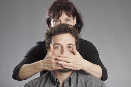 obscuring: Mature couple woman covering mans mouth Stock Photo