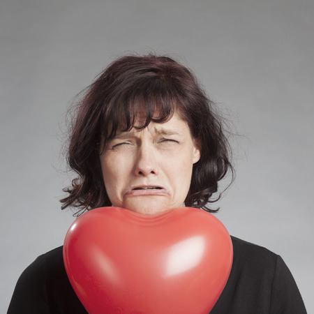 Sad brunette woman with heart shaped balloon against gray background