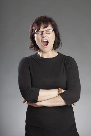 overstress: Mature brunette woman wearing glasses standing with hands folded yawning against gray background Stock Photo
