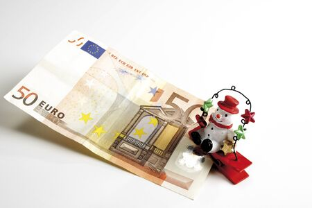 elevated view: Snowman sitting on Euro notes, elevated view Stock Photo