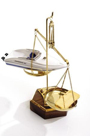 lingote de oro: Barra de oro y bote a motor en la escala Foto de archivo
