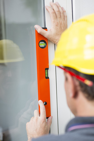 spirit level: Construction worker measuring windows straightness with spirit level Stock Photo
