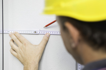 Construction worker drawing straight line using folding ruler photo