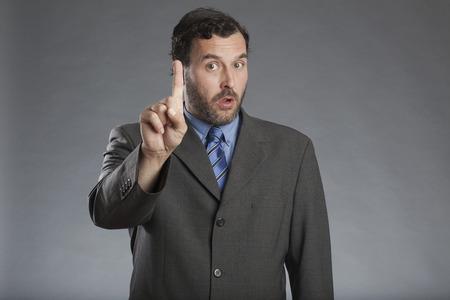 definite: Businessman holding index finger up against gray background