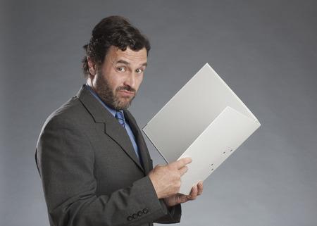 sceptical: Businessman holding folder against gray background