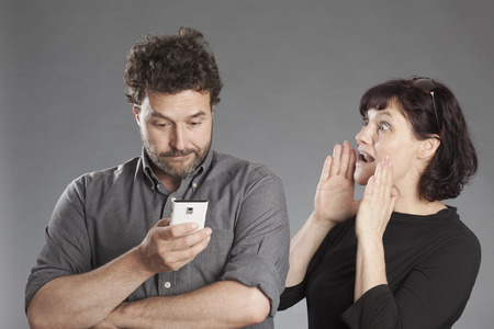 Mature couple man busy using smartphone woman shouting wanting attention photo