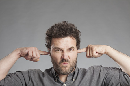 plugging: Annoyed mature man plugging ears with fingers Stock Photo