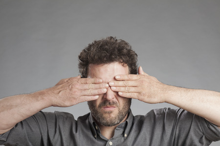obscuring: Mature man covering eyes