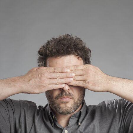 shutting: Mature man covering eyes