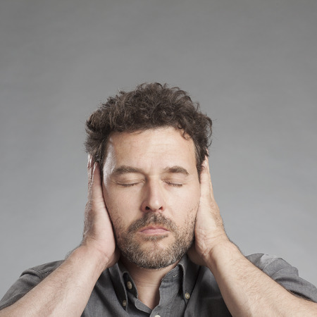 Mature man covering ears with hands photo
