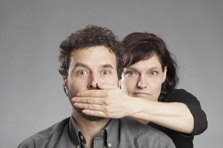 covering: Mature couple woman covering mans mouth Stock Photo
